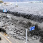 In this March 11, 2011 file photo, a tsunami floods over the breakwater protecting the coastal city of Miyako at Heigawa estuary area after northeastern Japan was hit by a powerful earthquake.