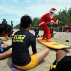 Photos: Santa Claus teaches orphans to surf in Bali